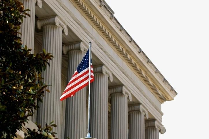 リハビリテーション法508条のブリーフィングを表現するためのアメリカ国旗が手前にある庁舎を引きで見た写真